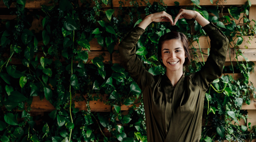 Woman standing near plants that are healthy and thriving, symbolising growth. Tips for growing a sustainable business